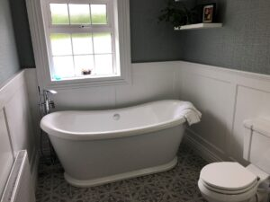 Traditional bathroom renovation in the South East with wood paneling and freestanding bath.